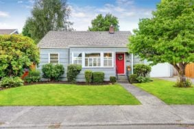 A cozy ranch-style house with a bright red front door and a nice yard, like the rental properties GTL Real Estate can provide Fayetteville property management for.