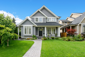 A beautiful house on a clear sunny day with a very green lawn, much like the rental properties GTL Real Estate can provide Roswell property management for.
